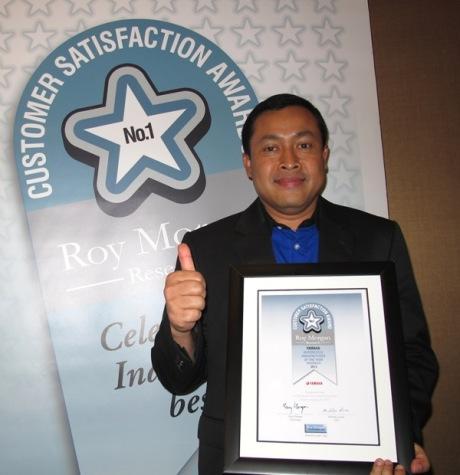 Direktur Sales Yamaha Indonesia Sutarya dengan piagam penghargaan Roy Morgan Award